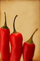 Three red chillis close up with a textured finish