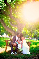 bride groom kissing on bench at sunset after wedding