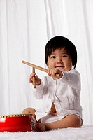 Chinese baby with red drum holding drum sticks