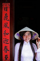 Young woman wearing traditional Vietnamese outfit standing next to a temple door