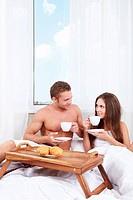 Young couple at breakfast in the bedroom