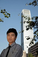 Portrait of young man standing in front of skyscraper, China
