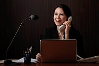 Chinese woman sitting at desk talking on phone and smiling