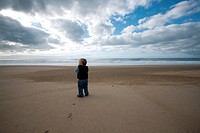 Toddler walking on beach, rear view