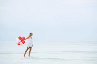 Woman walking on water, carrying bunch of balloons