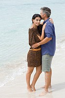 Husband and wife embracing on beach, ankles deep in water