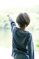 Boy looking at lake, pointing, rear view