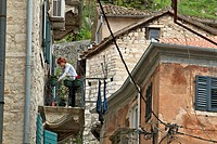 WOMAN ON HER BALCONY, OLD FORTIFIED TOWN OF KOTOR, THE BAY OF KOTOR, MONTENEGRO, EUROPE