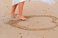 YOUNG WOMAN IN A BRIDAL GOWN BRIDE DRAWING A HEART IN THE SAND WITH HER FOOT