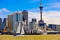 A sailboat sailing on Auckland Harbor with the Auckland skyline featuring the 328 meter high Sky Tower behind the tallest free-standing structure in t...