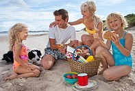 Family with dog picnicking on sunny beach