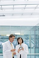 Engineers in lab coats examining part in office