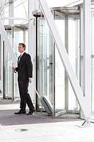 Businessman pulling suitcase through revolving door