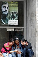 Three young girls talking under a banner with a picture of Fidel Castro in Havana, Cuba