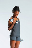African Woman Exercising With Dumbbells