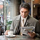 A man drinks coffee and reads the paper at a cafe