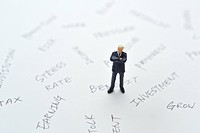 Miniature businessman surrounded by the words