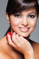 Young woman eating fresh strawberry