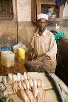 Fishmonger at city fish market, Stonetown, Unguja, Zanzibar, Tanzania