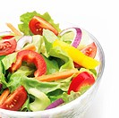 glass bowl of fresh mixed salad against white