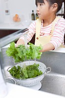 A girl washing lettuce