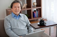 Senior man using laptop looking at camera
