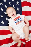 Caucasian baby laying on American flag