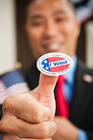 Chinese businessman holding out I Voted sticker (thumbnail)