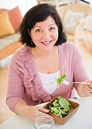 Hispanic woman eating salad for lunch