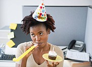 Black businesswoman blowing party blower at desk