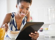 Black woman using digital tablet and eating cereal