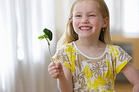 Grinning girl holding broccoli on fork