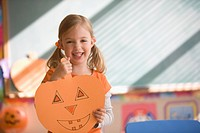 Caucasian girl holding drawing of pumpkin