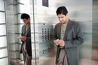 Indian businessman text messaging on cell phone in elevator
