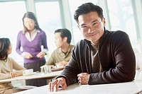 Smiling Asian man sitting in cafe