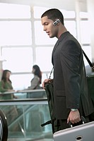 Hispanic businessman carrying suitcase and talking on hands_free cellular device