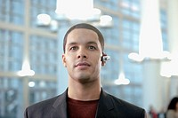Hispanic businessman wearing hands_free cellular device