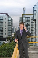Caucasian businessman using cell phone on city rooftop