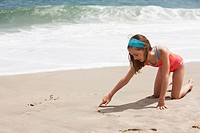 Caucasian girl drawing in the sand on beach