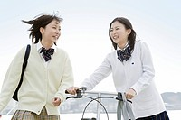 Two high school girls walking with a bicycle