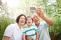 Chinese grandparents taking self_portrait with grandson