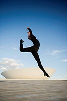 Brazilian dancer jumping in mid_air outdoors
