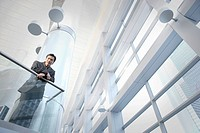 Asian businessman leaning on office railing