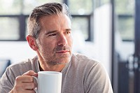 Serious Caucasian man drinking coffee