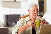 Senior Caucasian woman using laptop and drinking coffee
