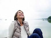 Germany, Munich, Mature woman sitting on jetty near lake, smiling
