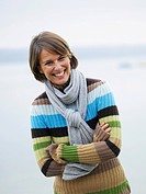 Germany, Munich, Mature woman near lake, smiling, portrait