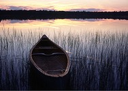 an open canadian canoe on a lake in canada made by native indians in Quebec