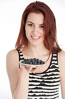 Studio shot of a young woman holding a plate with blueberries