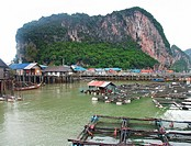 Phang Nga Bay boats and floating houses with limestone clifts in the background